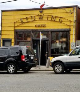 Entry to Redwing Cafe, with sidewalk and cars